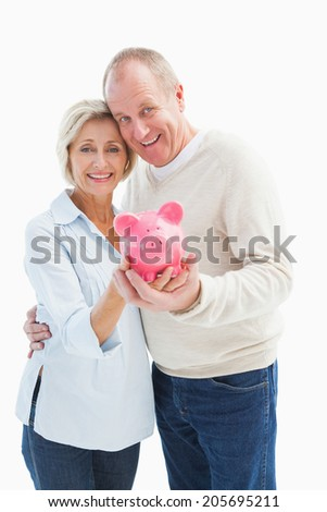 Happy mature couple smiling at camera showing piggy bank on white background - stock photo