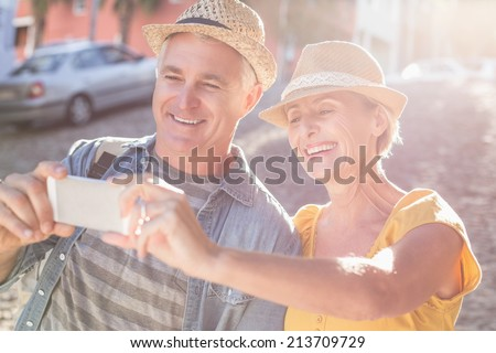 Happy mature couple taking a selfie together in the city on a sunny day - stock photo