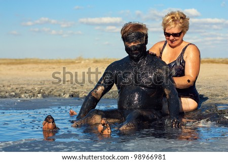 happy mature couple taking mud treatment outdoor on summer day