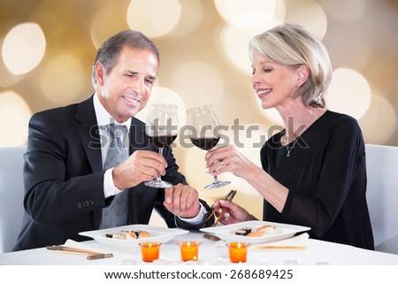 Happy Mature Couple Toasting Wine In A Elegant Restaurant - stock photo