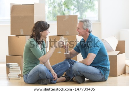 Happy mature couple toasting with champagne while sitting on floor in new house - stock photo