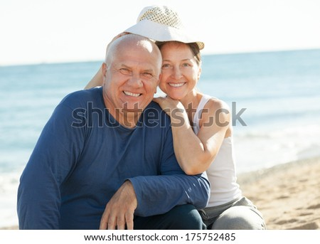 Happy mature couple together at sea sandy beach - stock photo