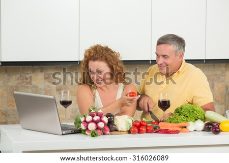 Happy mature couple using laptop computer in home. People are in search of recipes for preparing something from fresh vegetables in the kitchen. - stock photo