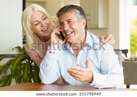 Happy mature couple using smartphone together at home in the kitchen - stock photo
