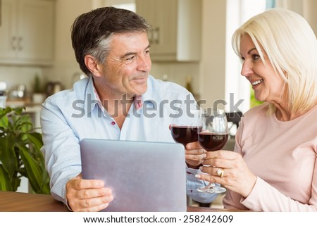 Happy mature couple using tablet drinking red wine at home in the kitchen
