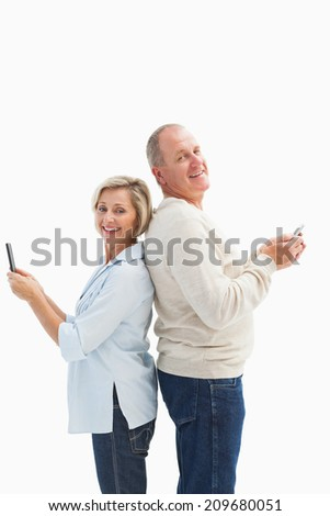 Happy mature couple using their smartphones on white background