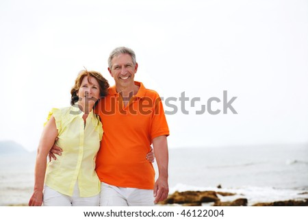 Happy mature couple walking along the beach. - stock photo