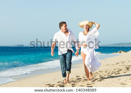 Happy mature couple walking on the beach