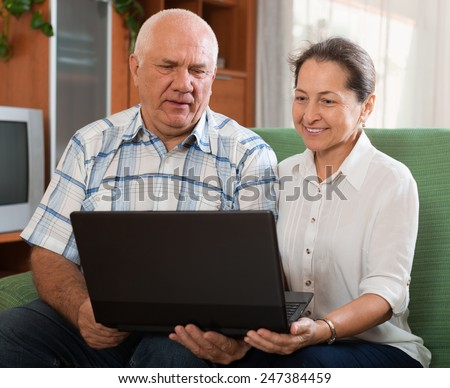 Happy mature couple  with computer  at table in home