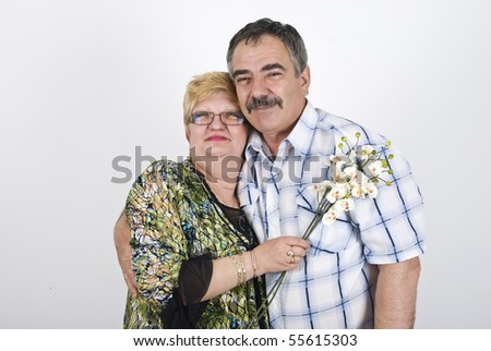 Happy mature couple with flowers  embracing and smiling - stock photo