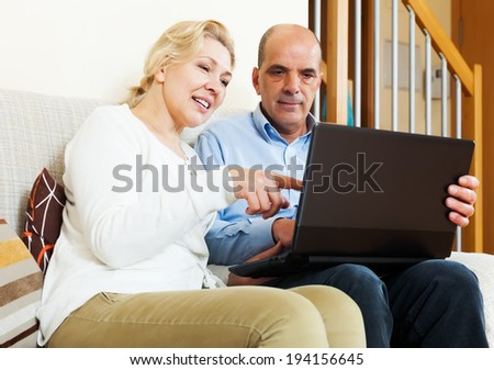 Happy mature couple with laptop at table at home - stock photo