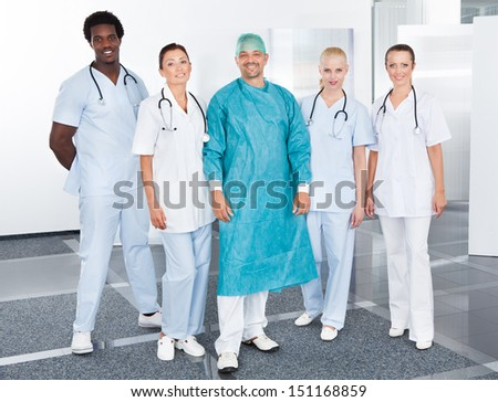 Happy Mature Doctor In Surgical Gown With His Coworkers - stock photo