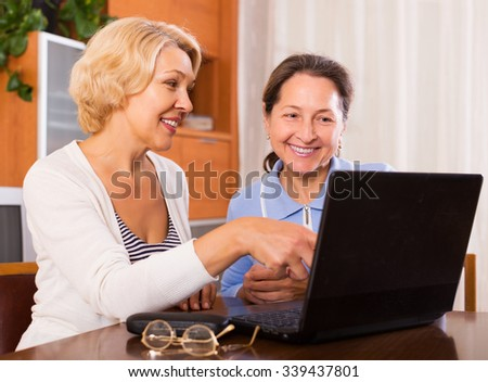 Happy mature female browsering web at home and smiling. Focus on blonde female - stock photo
