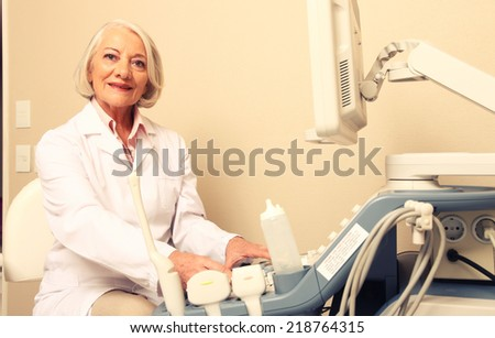Happy mature female doctor using ultrasound scanner. Echography machine. - stock photo