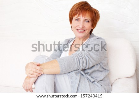 Happy mature female on sofa. Smiling middle woman at home