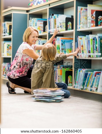 Happy mature female teacher and boy selecting books from bookshelf in library - stock photo