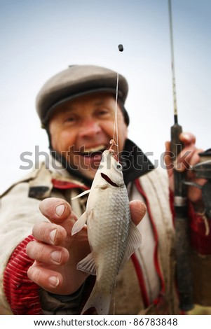 Happy mature fisherman with fresh caught crucian (Carassius of family Cyprinidae) on clear sky background - stock photo