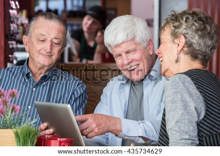 Happy mature friends on wifi with tablet computer in a coffeehouse - stock photo
