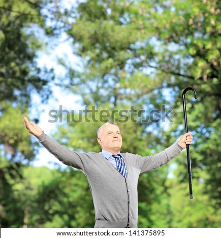 Happy mature gentleman holding a cane and spreading his arms in a park - stock photo