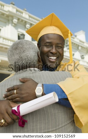 Happy mature graduate hugging father in font of university - stock photo