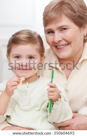 Happy mature grandmother is embracing a small child. The girl is holding a pencil and eating cookie. They are looking at camera and smiling - stock photo
