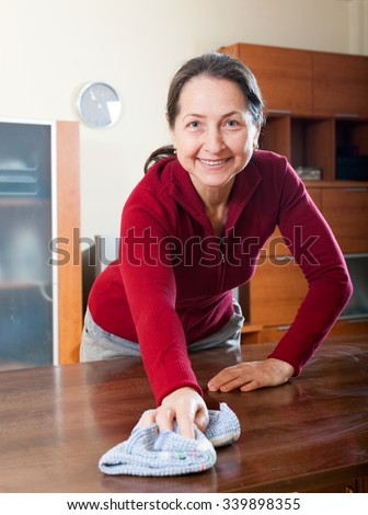 Happy mature housewife cleaning table with cleanser and rag at living room