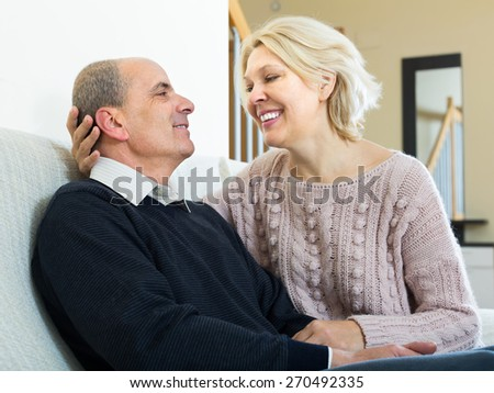 Happy mature husband and wife cuddling on couch at home  - stock photo
