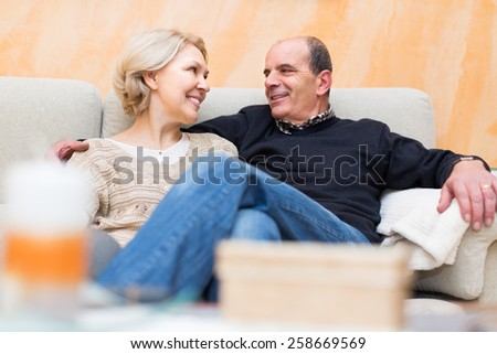 Happy mature husband and wife cuddling on couch at home. Focus on woman - stock photo