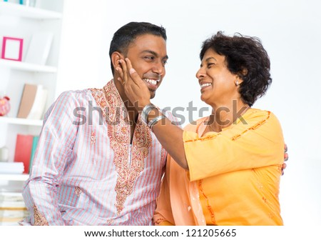 Happy mature Indian woman with her adult son - stock photo