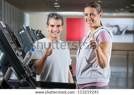 Happy mature instructor and female client showing thumbs up sign in health club - shallow depth of field, focus on trainer