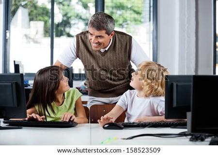 Happy mature male teacher assisting schoolchildren in using desktop PC at computer lab - stock photo