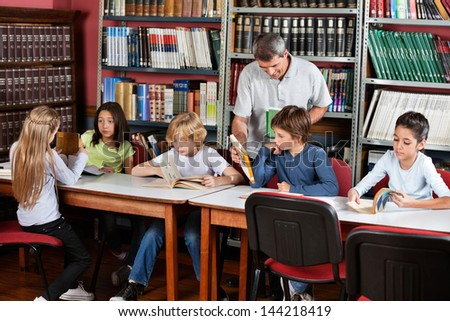 Happy mature male teacher showing book to schoolboy with students studying at table in library - stock photo