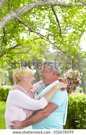 Happy mature man and woman looking at one another and laughing in park