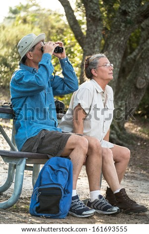 Happy mature man and woman resting at a picnic table at a campsite, watching birds with binoculars. - stock photo