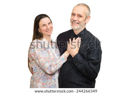 Happy mature man and woman with long hair smiling for S. Valentine's day or anniversary and putting the hands on the heart. Isolated on white background.