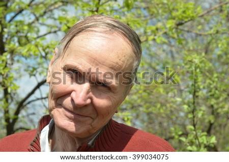 happy mature man closeup portrait over trees background. people concept - stock photo