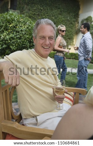 Happy mature man holding glass of wine with friends