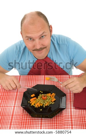 Happy mature man on a diet eating his vegetables - stock photo