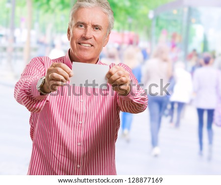 Happy Mature Man Showing Blank Placard against a street background - stock photo