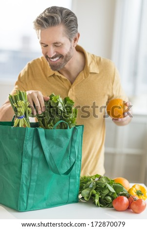 Happy mature man unpacking bag of groceries at counter top