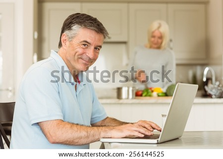 Happy mature man using laptop at home in the kitchen - stock photo