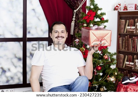 Happy mature man with gift near a christmas tree - stock photo