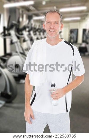 Happy Mature Man With Towel On Shoulder Holding Bottle Of Water At Gym - stock photo
