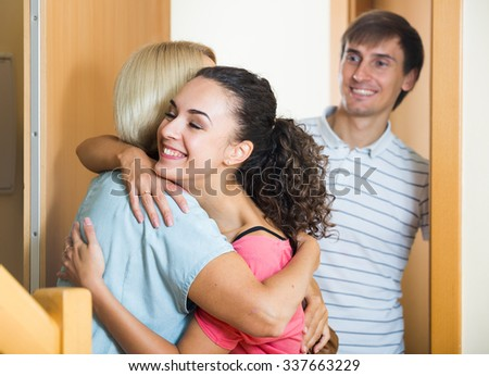 Happy mature mother meets son with his wife at doorway