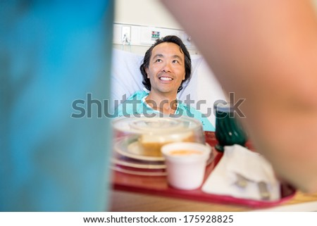 Happy mature patient looking at nurse serving breakfast in hospital - stock photo