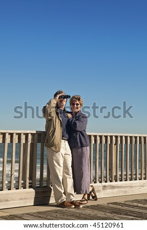 Happy mature, senior couple on a wooden seaside pier with the ocean in the background. - stock photo