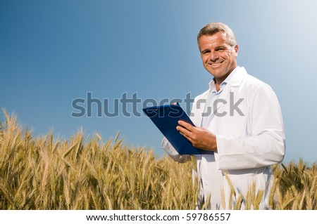 Happy mature technician checking the growth of the wheat for a quality control in a cereal field in summer - stock photo