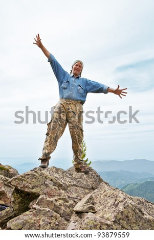 Happy mature the man costs at top of mountain, having stretched hands in sides - stock photo