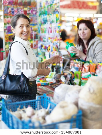 Happy mature  woman buys liquid fertilizer at store - stock photo