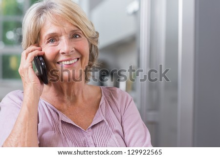 Happy mature woman calling in the kitchen - stock photo